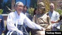 지난해 7월 위안부 피해자 김복동 할머니가 미국 글렌데일 시립 도서관 앞에서 제막한 평화의 소녀상 옆에 앉아 소녀상을 쓰다듬고 있다. (자료사진)