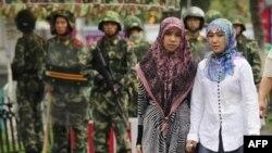 資料照:在新疆烏魯木齊市的兩名維吾爾族婦女步行經過中國武警隊伍。