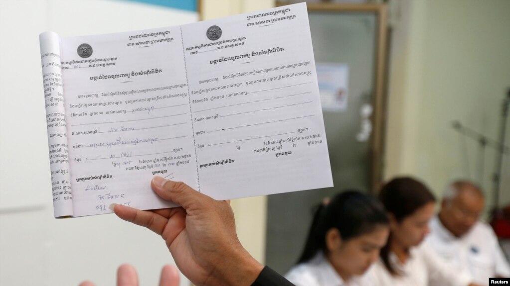 Thành viên của Ủy ban bầu cử quốc gia Campuchia và người phát ngôn Dim Sovannarom đưa ra danh sách các đảng đã đăng ký tranh cử tại Phnom Penh, ngày 30/4/2018.