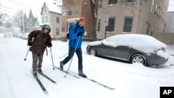Andre Tranchemantague (kiri) dan Will Guerette, menggunakan peralatan ski mereka melaju di jalan yang tertutup salju di kota Portland, negara bagian Maine, Jumat (8/2).
