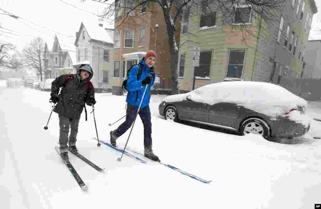 Andre Tranchemantague, left, and Will Guerette, ski on a snow-covered road in Portland, Maine, Feb. 8, 2013.