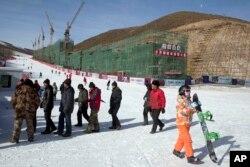 河北省一座滑雪场上的民工、滑雪者和正在建造的滑雪公寓。如果北京获得冬奥主办权,部分比赛将在这里举行(2014年12月6日)
