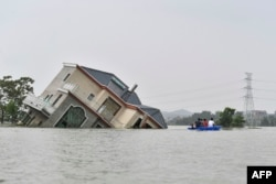 This photo taken on July 15, 2020 shows residents riding a boat past a damaged and flood-affected house near the Poyang Lake due to torrential rains in Poyang county, Shangrao city in China's central Jiangxi province.