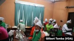 Des employées en train de suivre des explications de la patronne dans la salle de production des coussins menstruels à Minna, la capitale de l'Etat du Niger, à 160 km d'Abuja, Nigeria, 13 octobre 2018. (VOA/Gilbert Tamba)