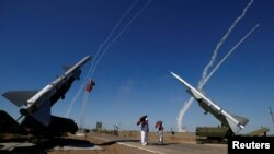 FILE - Missiles are launched at the International Army Games 2017 at the Ashuluk shooting range outside Astrakhan, Russia, Aug. 5, 2017. The United States says Russia must scrap or modify some of its weapons in order to remain in compliance with a key arms control treaty.