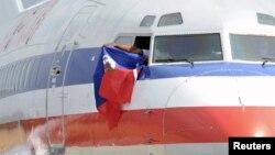 Yon pilòt nan yon vòl American Airlines kap flote drapo ayisyen an deyò fenèt avyon an ki te soti Miami e ki tap ateri nan Aewopò Entènasyonal Toussaint Louverture nan Pòtoprens, Ayiti, 19 fevriye, 2010.