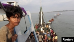 A fishing boat carrying Rohingya and Bangleshi migrants is pulled to shore by Achenese fisherman off the coast of Julok, in Aceh province, May 20, 2015.