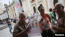 Seorang pria memegang poster yang menunjukkan surat suara di tengah kota Caracas, Venezuela, 5 Desember 2015.