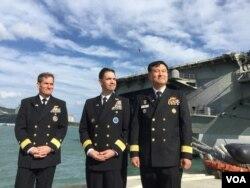 미 해군 제5항모강습단이 부산 해군기지에 입항한 지난 21일 달튼 5항모강습단장(왼쪽부터), 쿠퍼 주한 미 해군사령관, 한국 작전사 참모장이 핵 추진 항공모함 로널드 레이건호를 배경으로 서 있다.