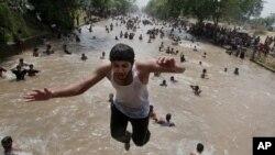 Seorang anak laki-laki melompat ke sebuah kanal di Lahore, Pakistan, di tengah gelombang panas yang mencapai 46 derajat Celsius. (Foto: Dok)