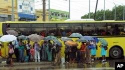 23일 자메이카 킹스턴에서 우산을 쓰고 버스를 기다리는 주민들.