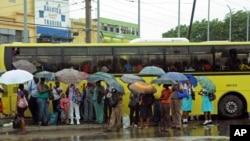 Hành khách chờ xe dưới mưa ở Jamaica, ngày 23/10/2012
