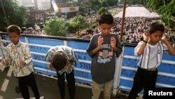 Ilustrasi. Anak-anak sedang melakukan salat di atas jembatan sementara orang dewasa menempati jalan untuk menyambut perayaan Muslim Idul Fitri. (Foto: Reuters)