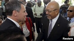 Suriname's President Desi Bouterse (R) is congratulated by Brazil's ambassador to Suriname, Marcelo Baumbach, after he was re-elected to office by the National Assembly in Paramaribo, July 14, 2015.