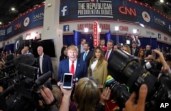 FILE - Donald Trump is joined by his wife, Melania, in the spin room following the CNN Republican presidential debate in Las Vegas, Dec. 15, 2015.