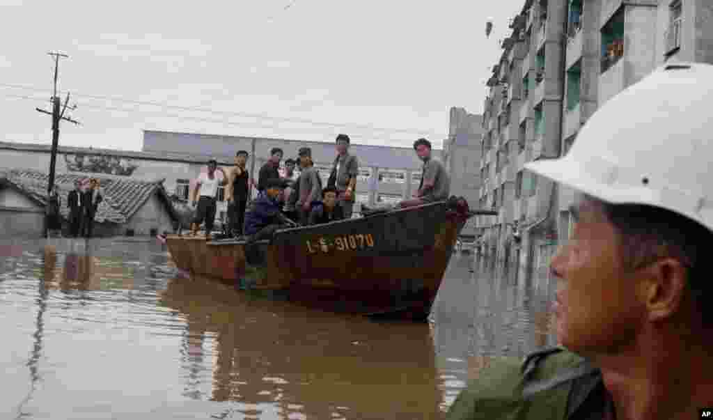 A rescue boat sails through a flooded street in Anju City, South Phyongan Province, North Korea, July 30, 2012.