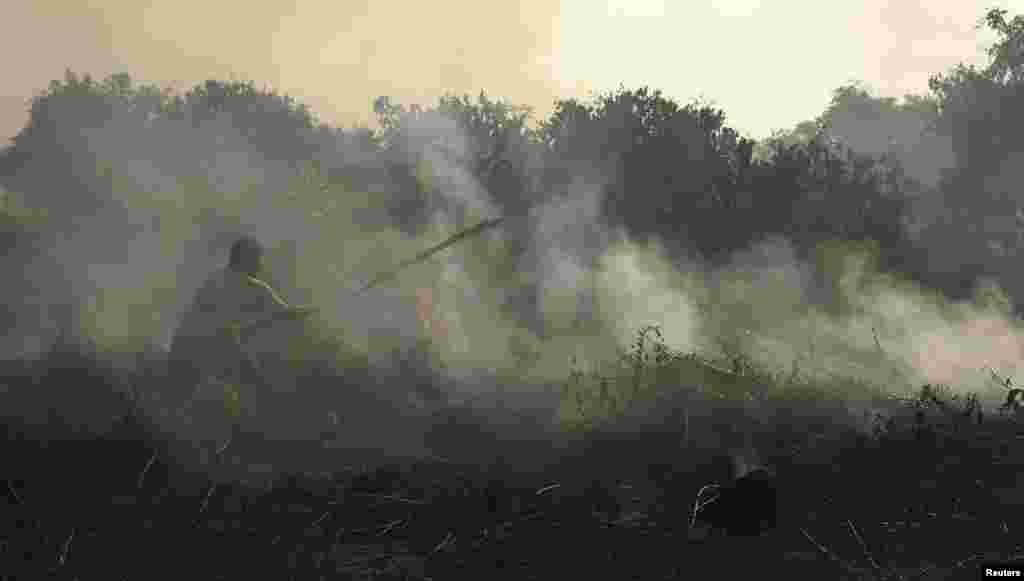 A resident tries to extinguish a fire burning on peatland in Pekanbaru of Riau province June 24, 2013.