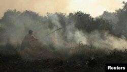 Warga berusaha memadamkan api yang membakar lahan gambut di hutan di Pekanbaru, Riau. (Foto: Dok)
