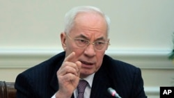 Ukrainian Prime Minister Mykola Azarov gestures while speaking during a cabinet meeting in Kiev, Ukraine, Wednesday, Dec. 18, 2013.
