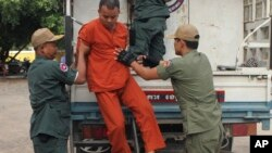 Yem Chroeum, center, an unlicensed medical practitioner, is assisted by prison guards to get off a truck upon his arrival at the Battambang provincial court in Battambang province, northwest of Phnom Penh, Cambodia, Thursday, Dec. 3, 2015. The Cambodian c