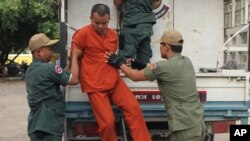 FILE PHOTO - Yem Chroeum, center, an unlicensed medical practitioner, is assisted by prison guards to get off a truck upon his arrival at the Battambang provincial court in Battambang province, northwest of Phnom Penh, Cambodia, Thursday, Dec. 3, 2015.
