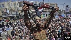 Một sĩ quan quân đội Yemen giơ cao khẩu súng AK-47 sau khi ông cùng các sĩ quan khác gia nhập đoàn biểu tình chống chính phủ hôm 21/3/11