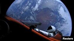 Mobil Tesla Roadster berwarna merah mengangkasa setelah diterbangkan ke antariksa oleh roket Spacex, Falcon Heavy, 9 Februari 2018. (SpaceX via Reuters)