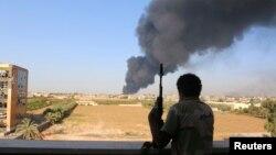Một chiến binh thuộc lực lượng dân quân Hồi giáo Zintan đứng nhìn cuộn khói từ bồn nhiên liệu bốc cháy do bị tên lửa bắn trúng ở Tripoli, ngày 2 tháng 8, 2014.