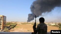 Seorang pejuang dari brigade Zintan menonton asap yang membumbung setelah roket diledakkan oleh salah satu militan Libya dan meledakkan tank minyak di Tripoli, 2 Agustus 2014.