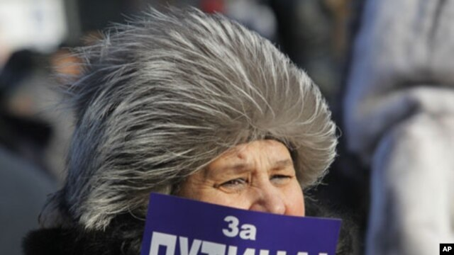 "A demonstrator holds a poster reading: ""For Putin!"" during a rally in support of Putin's candidacy to the presidency in the March 4th election, in St.Petersburg, Russia, Saturday, Feb. 18, 2012."