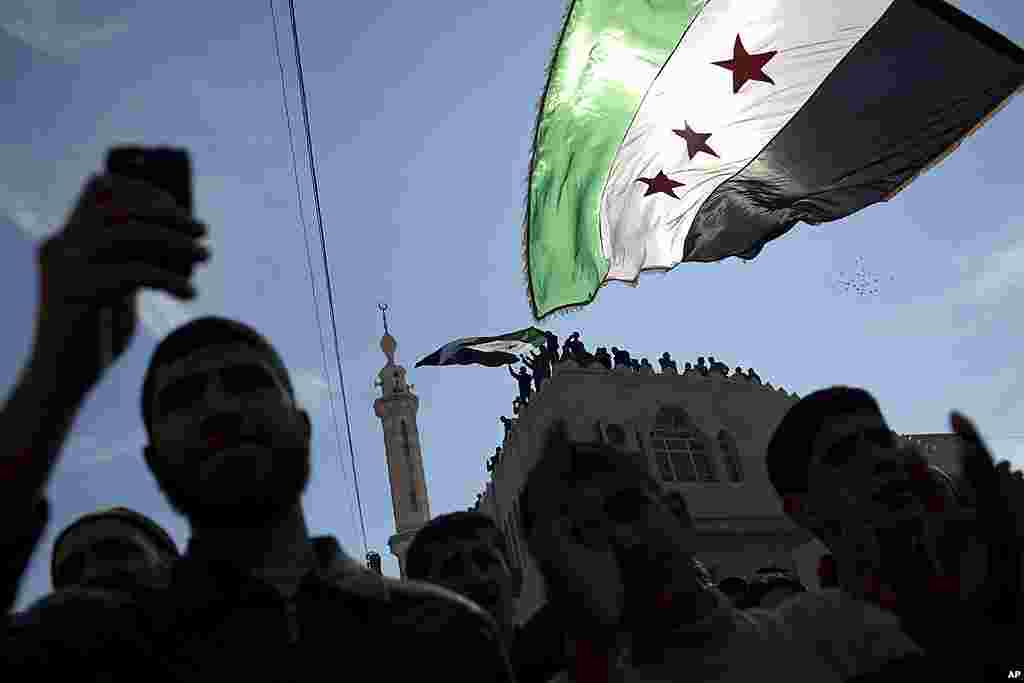Men hold revolutionary Syrian flags during an anti-government protest in a town in north Syria on March 2, 2012. (AP)