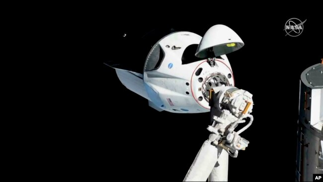 FILE - The SpaceX Crew Dragon capsule is pictured, March 3, 2019, about 20 meters (66 feet) from the International Space Station's Harmony module. SpaceX said May 2, 2019, that their Dragon capsule for astronauts was destroyed during a ground test, April 20, 2019.