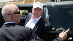 Presidential candidate Donald Trump talks to protesters as he leaves the World Trade Bridge border crossing in Laredo, Texas, July 23, 2015.