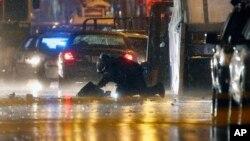 2014年4月15日,一名爆炸組調查人員在波士頓馬拉松賽的終點線附近檢查兩個沒有人認領的背包。