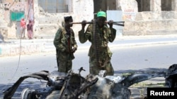 Somali government soldiers look at the wreckage of a mangled car used by a suicide bomber at the scene of a bomb attack next to a tea shop in the suburbs of capital Mogadishu February 27, 2014.