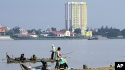 People fish on wooden boats on the Mekong River in Phnom Penh, Aug. 19, 2010. (file photo)