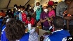 Migran Haiti yang dideportasi dari Texas dan baru tiba di bandara Toussaint Louverture di Port-au-Prince ditemui oleh petugas organisasi migran PBB (IOM) (foto: dok).