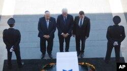 L'ancien président américain Bill Clinton, au centre, accompagné du président Reuven Rivlin d'Israël, à gauche, et Yuli Edelstein, le Président de la Knesset, s'inclinent devant le cercueil de l'ancien président israélien Shimon Peres à la place de la Knesset à Jérusalem, 29 septembre 2016.