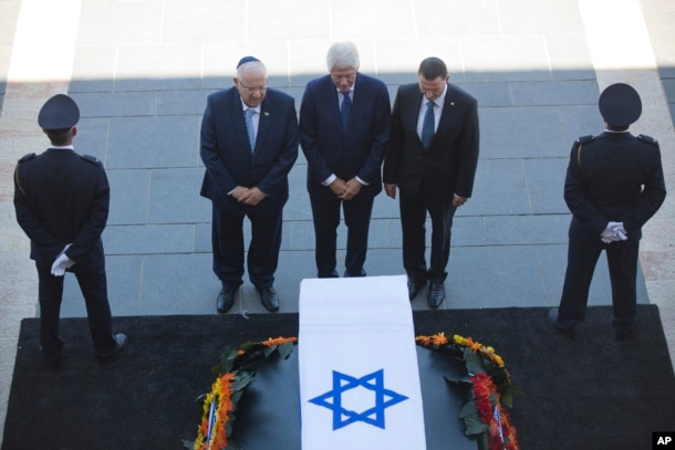 Former US President Bill Clinton, center, accompanied by Israel's President Reuven Rivlin, left, and Yuli Edelstein, the Speaker of the Knesset, pays respects by the coffin of former Israeli President Shimon Peres at the Knesset plaza in Jerusalem.