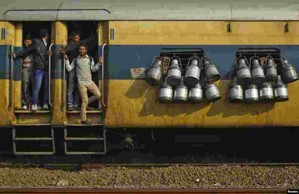 Commuters stand on the door of a passenger train as milk containers hang on the windows in Ghaziabad, on the outskirts of New Delhi, India.