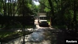 A still image taken from a video footage shows trucks packed with furniture and diplomats' belongings leaving a dacha compound used by U.S. diplomats for recreation, in Serebryany Bor residential area in the west of Moscow, Russia, Aug. 1, 2017.