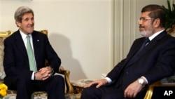 Menlu AS John Kerry (kiri) dalam pertemuan dengan Presiden Mesir Mohamed Morsi di Kairo, hari Minggu (3/3).