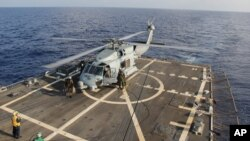 A U.S. Navy helicopter lands aboard Destroyer USS Pinckney during a crew swap before returning to a search and rescue mission for the missing Malaysian airlines flight MH370 in the Gulf of Thailand, Sunday, March 9, 2014.