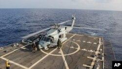 """美国海军一架直升机在暹罗湾参加失踪马航班机搜救任务后在""""平克尼号""""导弹驱逐舰着陆换班。(2014年3月9日)"""