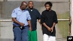 Uno de los 32 escapados (derecha) regresa a prisión tras ser devuelto por su familia.