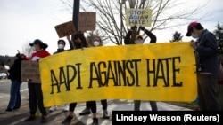 """华盛顿州的一群活动人士高举""""亚太裔反对仇视""""标语 (路透社 2021年3月17日)"""