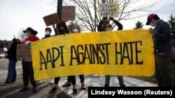 """Người biểu tình giăng biểu ngữ với khẩu hiệu """"Cộng đồng AAPI chống Hận thù Chủng tộc"""" tại một cuộc tuần hành để phản đối các tội ác vì hận thù người gốc Á tại Newcastle, Washington, Ngày 17/3/2021. (REUTERS/Lindsey Wasson)"""