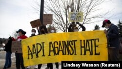 "People wave a large ""AAPI Against Hate"" sign at honking cars during a pre-planned rally against anti-Asian hate crimes held by the Asian American Pacific Islanders Organizing Coalition Against Hate and Bias in Newcastle, Washington, U.S."