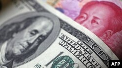 Tờ giấy bạc 100 đồng nguyên của Trung Quốc đặt dưới tờ giấy bạc 100 đôla Mỹ