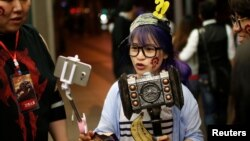 """FILE - A fan livestreams her participation during China's premiere of the film """"Warcraft"""" at a theater in Shanghai, China, June 7, 2016."""